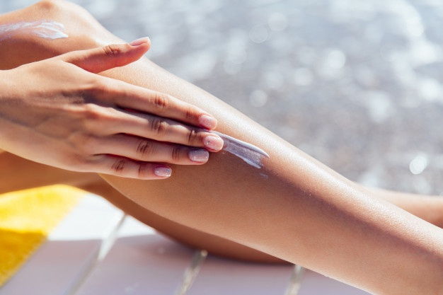 close-up-view-female-hand-applying-sunscreen-her-leg-near-sea_8353-6285