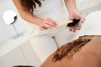woman-cleans-skin-body-with-coffee-scrub-spa-wellness-center_1139-1707